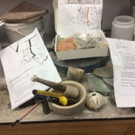 Maps and notes on bench with mortar & pestle used to grind all the inclusions.
