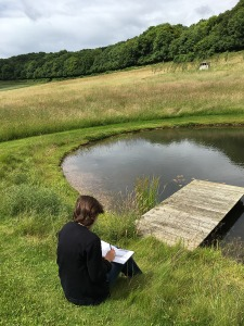 Katherine Jones sitting drawing at the Rabley Drawing Centre pond.